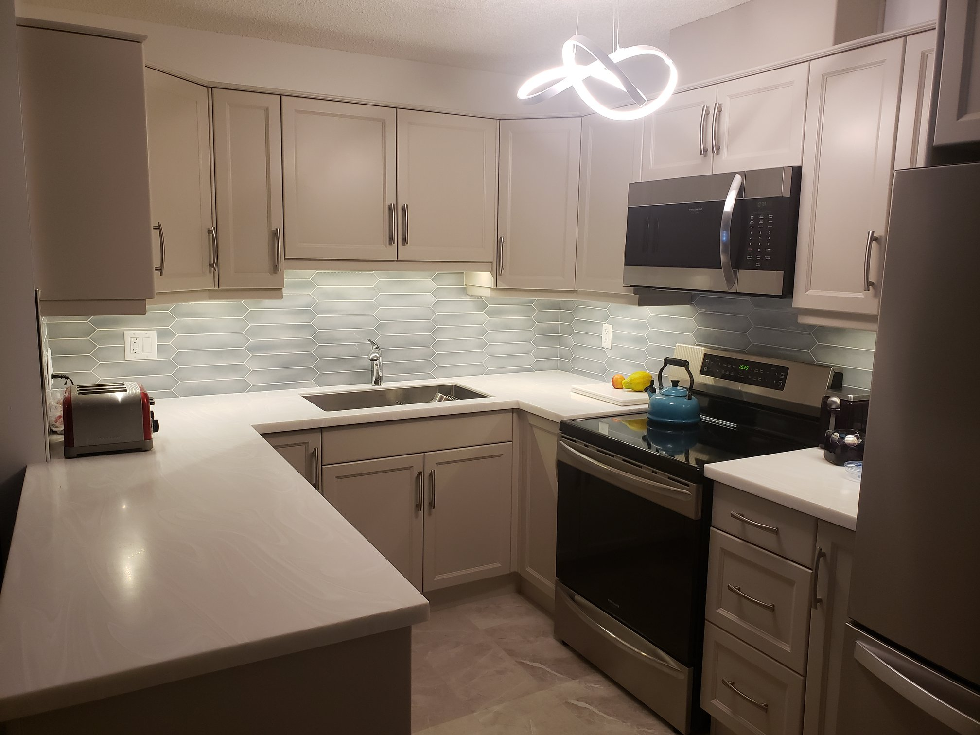 The finished kitchen was a major style upgrade. The cabinets, by Bigstone Custom Cabinets are in a color called shaker and the counter top was supplied by PF Custom Countertops and is Corian, White Onyx.