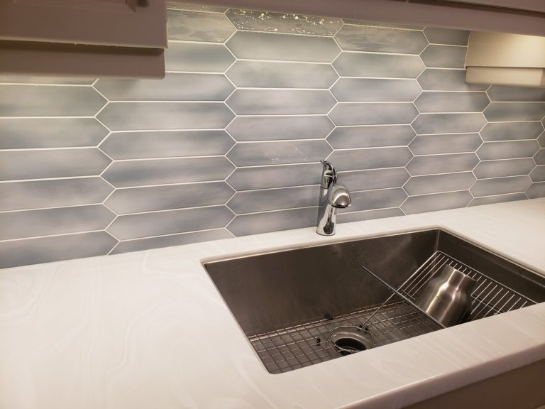 Here is a close up of the backsplash and the kitchen sink. My client opted for a large single stainless steel undermount basin and a chrome set of Moen taps.