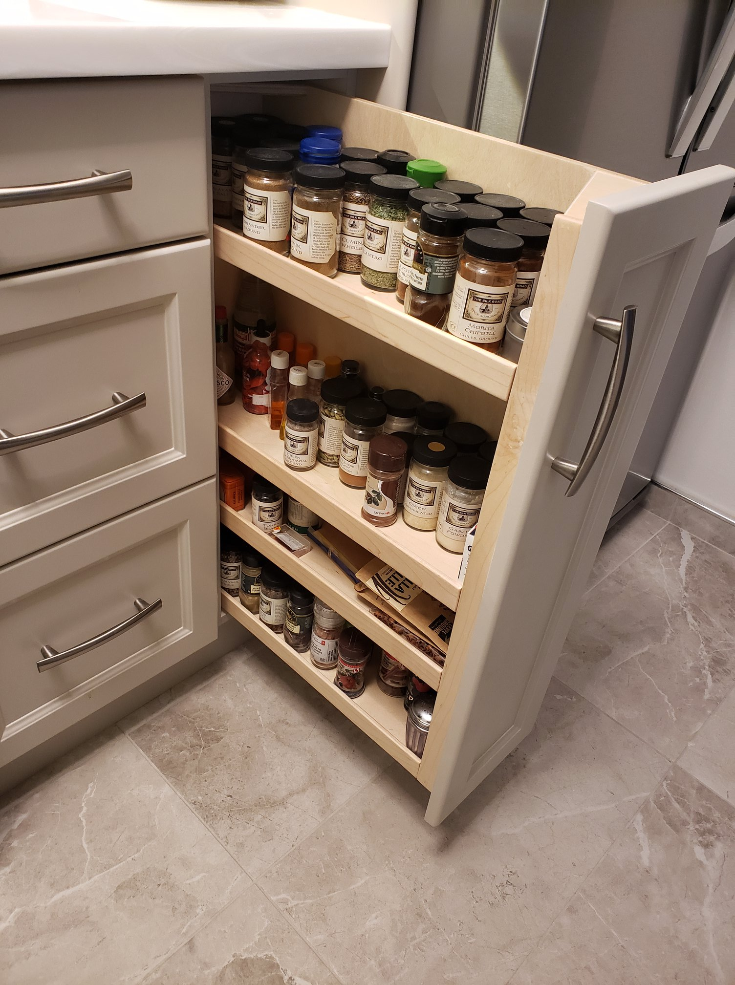 Here is the pull out spice rack all loaded up with my client's spices for cooking.